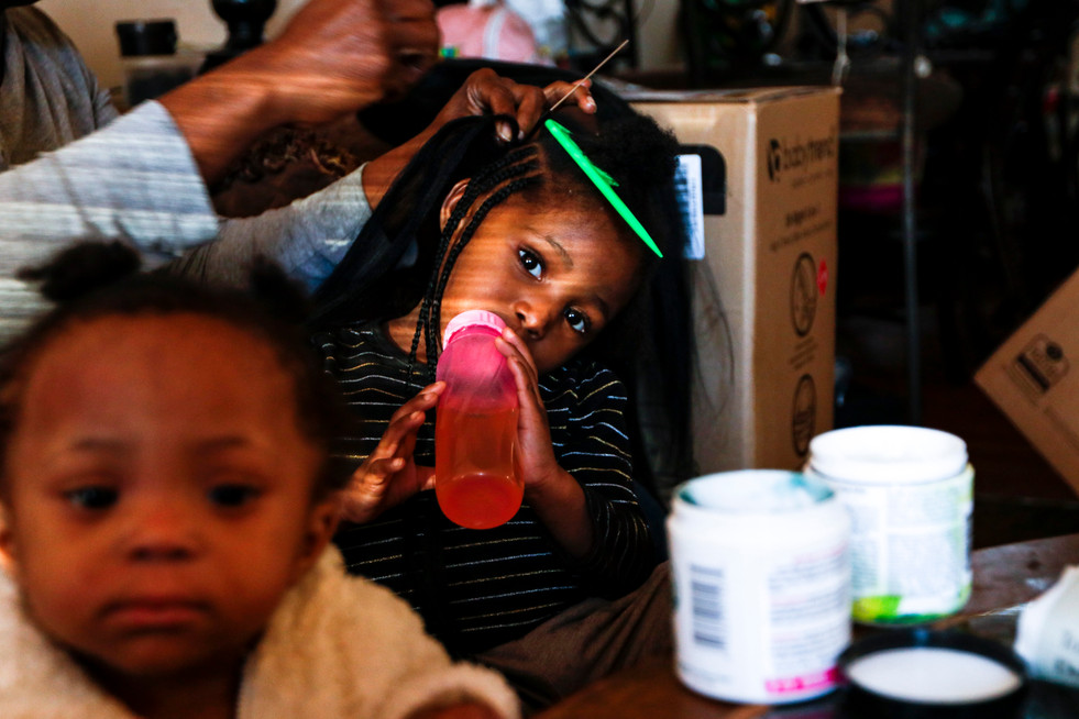 Renata Hailey braids her two-year-old daughter's hair while her one-year-old daughter toddles around the living room in Athens, Georgia on Thursday, Feb. 27, 2020. Hailey has been vocal about maintenance oversights at her apartment complex, speaking to local reporters and allowing her name to be published in investigative reports despite risks that her landlord could evict her for speaking out.
