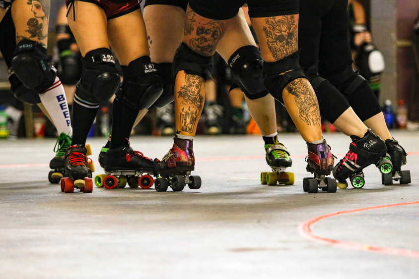 Roller derby skaters in a pack attempt to block the opposing team's jammer from passing them and scoring points at the Athens Arena on Aug 17, 2019. Skaters with a star on their helmet, known as jammers, are allowed to score points for their team by breaking through the pack and racing around the track.