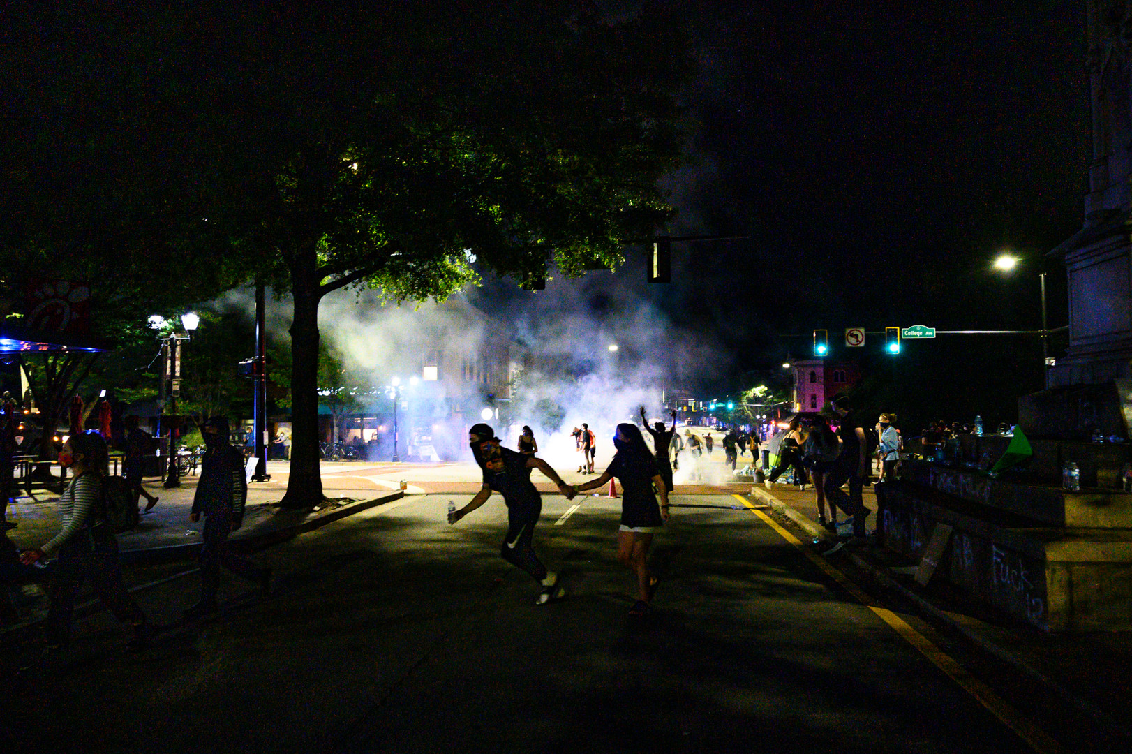 Protestors run as police fire tear gas in Athens, Georgia just after midnight on Monday, June 1, 2020. Two non-violent protests started in the afternoon, both calling for racial justice and an end to police brutality following the death of George Floyd in Minneapolis six days earlier. As the evening progressed, police forces surrounded the intersection with armored trucks, officers in riot gear and police cars.