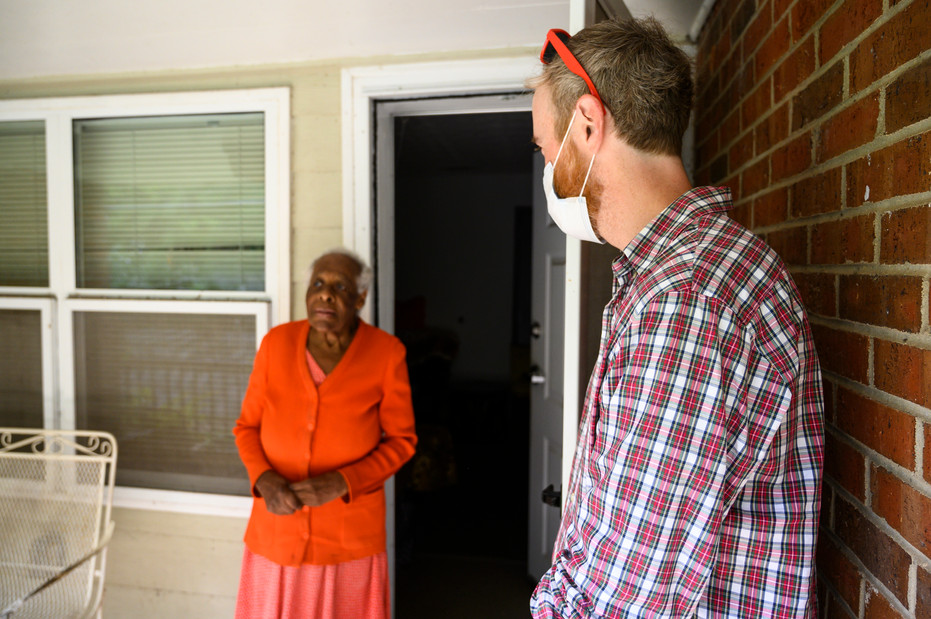 Athens Community Council on Aging volunteer Carey McLaughlin converses with Lorene Young, the resident of the final home on his Meals on Wheels route in Athens, Georgia on Wednesday, July 29, 2020.
