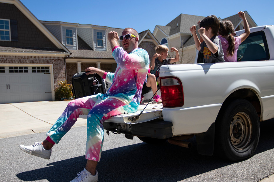Joey Stewart dances in a unicorn costume with his kids and their neighborhood friends as his wife drives their truck around their Athens, Georgia neighborhood on Saturday, April 23, 2020.