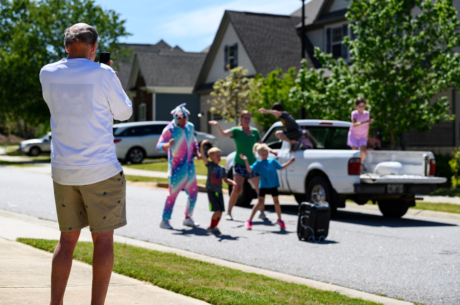 A neighbor steps off of his porch to take a video of the Stewart family's dance routine in Athens, Georgia on Saturday, April 23, 2020.