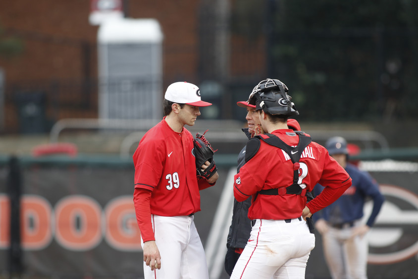 Redshirt sophomore Darryn Pasqua and sophomore Shane Marshall talk with coach Scott Stricklin during a decisive moment on Foley Field in Athens, Georgia on Sunday, Feb. 16, 2020. In their third game of the series, the UGA baseball team beat the University of Richmond Spiders 5-4 to sweep the series.
