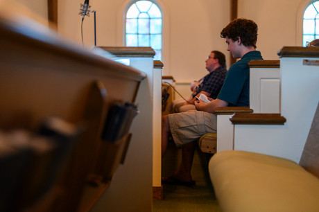 Nathan Bailey opens a bible at Winterville First Baptist Church in Winterville, Georgia on Sunday, May 24, 2020. As part of the worship team, Bailey was one of a small group allowed in the church building for the production of their live streamed services.