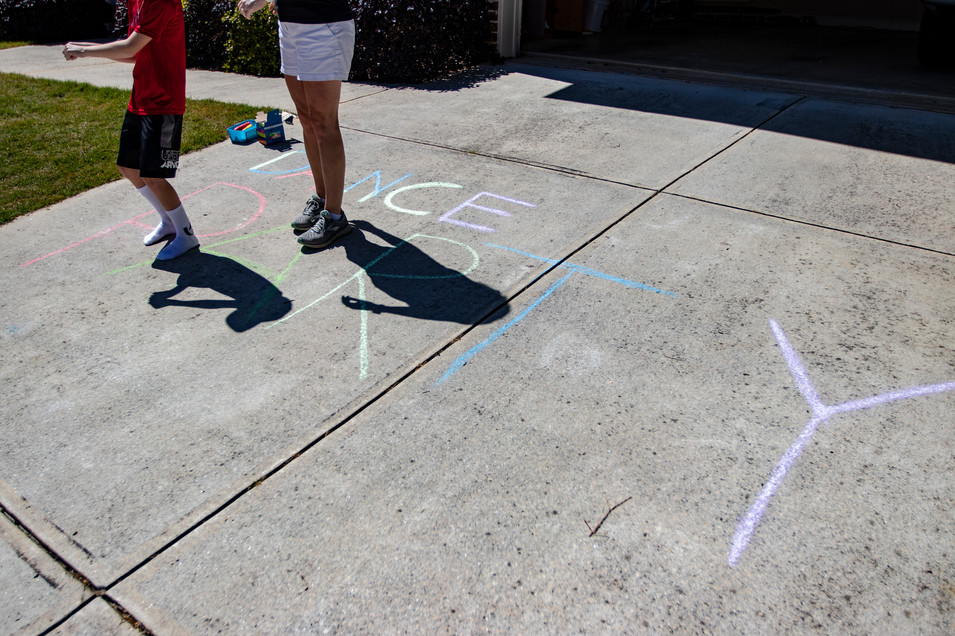 A family prepared for the weekly neighborhood dance party with chalk drawings in their driveway in Athens, Georgia on Saturday, April 23, 2020.