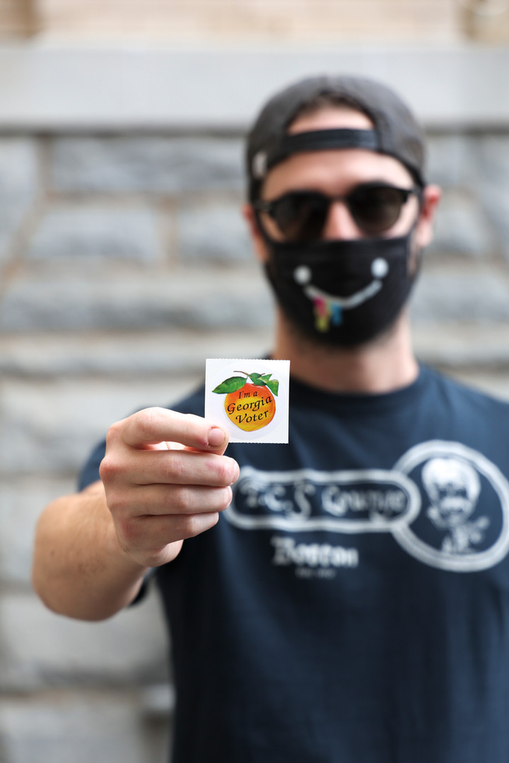 """Nik Partridge holds his """"Georgia voter"""" sticker after voting early in Athens, Georgia on Thursday, Oct. 22, 2020 in the general election scheduled for November 3, 2020. This was Partridge's first time voting."""