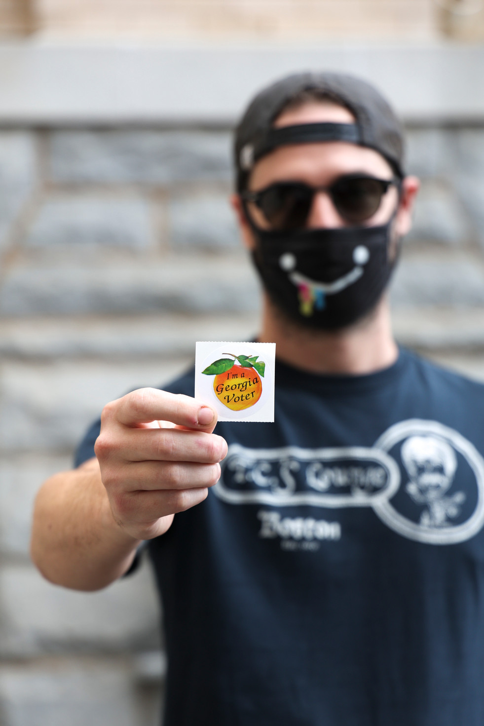 "Nik Partridge holds his ""Georgia voter"" sticker after voting early in Athens, Georgia on Thursday, Oct. 22, 2020 in the general election scheduled for November 3, 2020. This was Partridge's first time voting."