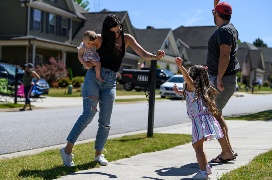 Laura and Matthew Perkins dance in their front yard with their two daughters, 4-year-old Emmy and 7-month-old Violet  in Athens, Georgia on Saturday, April 23, 2020.