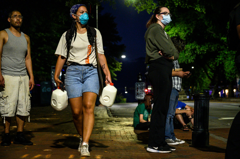 A protester carries gallons of milk to combat the effects of tear gas in Athens, Georgia on Sunday, May 31, 2020. Two non-violent protests joined together at the symbolic University of Georgia arch, both calling for racial justice and an end to police brutality following the death of George Floyd in Minneapolis six days earlier.