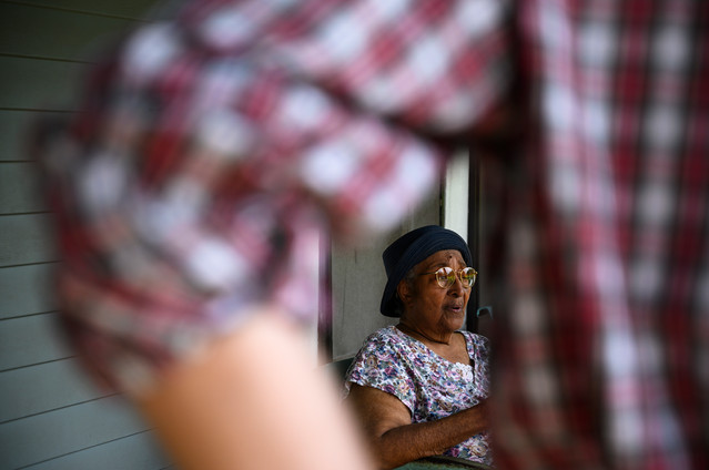 After delivering a box of meals, Athens Community Council on Aging volunteer Carey McLaughlin talks with Mildred Huff on her front porch while on his Meals on Wheels route in Athens, Georgia on Wednesday, July 29, 2020. Huff has lived in this home for over 50 years, and McLaughlin chats with her each week.