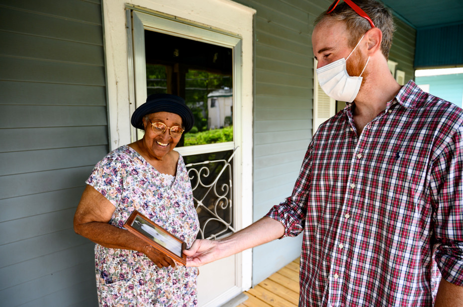 Mildred Huff shows ACCA volunteer Carey McLaughlin a photo of her oldest son while they chat on her front porch in Athens, Georgia on Wednesday, July 29, 2020. Huff has lived in this home for over 50 years, and McLaughlin chats with her each week while on his Meals on Wheels route.
