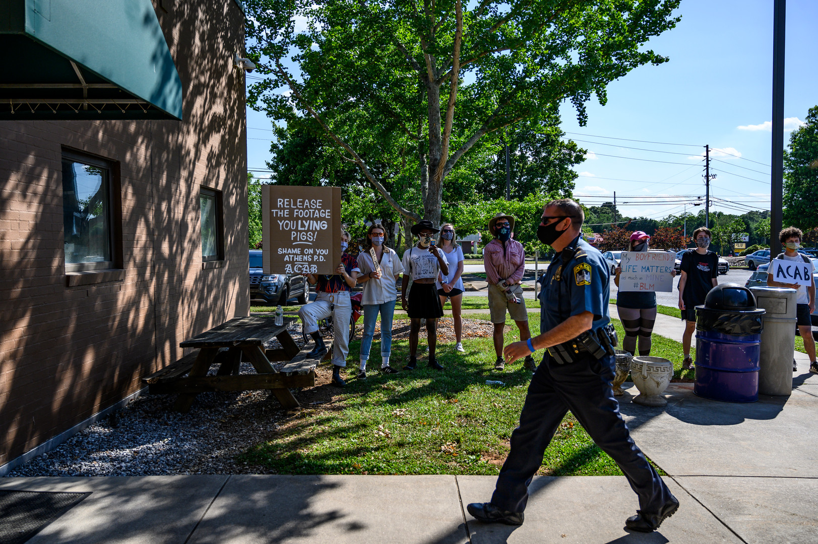 An Athens-Clarke County police officer enters the East Precinct building on Friday, June 12, 2020 in Athens, Georgia. Protesters holding signs and chanting for the release of footage from the night they were tear gassed waited outside the building for officers to exit for the day.