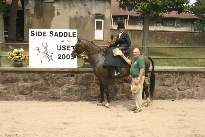 Laureen side saddle with Roger presenting Age of Elegance Award