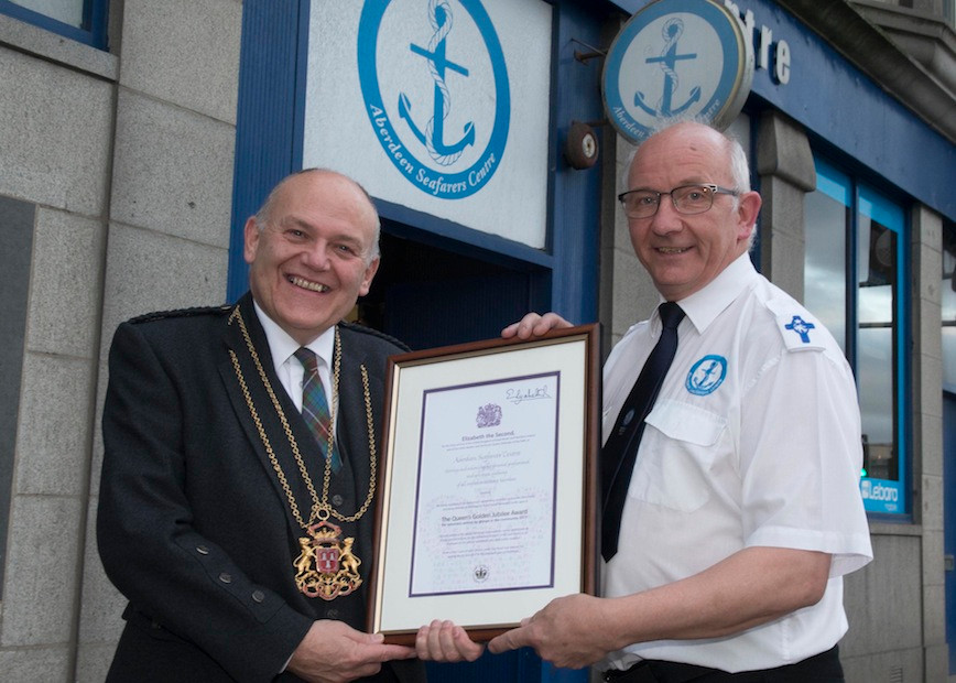 •	The Lord Lieutenant of Aberdeen, Councillor Barney Crockett presented a Queen's Award for Voluntary services to the volunteers at the Aberdeen Seafarers' Centre. Receiving the award was Pastor Howard Drysdale. 	Photo credit: Norman Adams-Aberdeen City Council