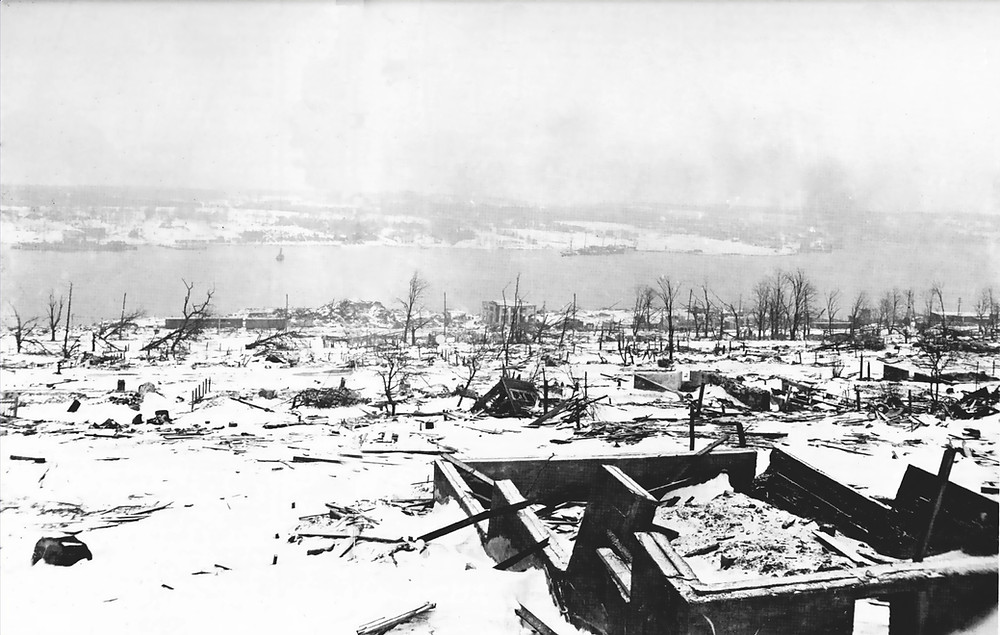 A view across the devastated neighbourhood of Richmond in Halifax, Nova Scotia after the Halifax Explosion, looking toward the Dartmouth side of the harbour. The steamship Imo, one of the ships in the collision that triggered the explosion can be seen aground on the far side of the harbour - Halifax after 6th December 1917