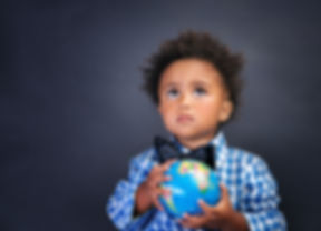 Portrait of cute little African boy holding in hands small globe on blackboard background, back to s