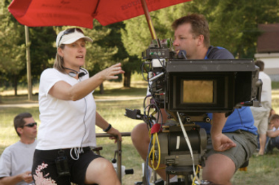 Alexandra sits behind a camer talking to the Director of Photography.