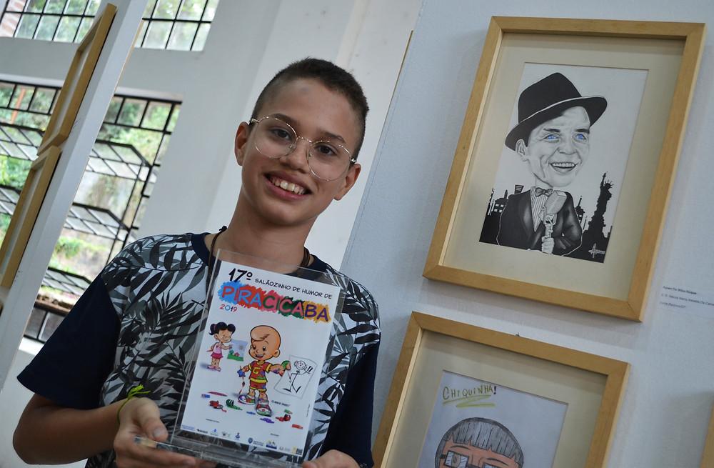 Ayran da Silva Roque, 14 anos, com o troféu e ao lado de sua obra vencedora na categoria 11 a 14 anos - Imagem: Rafael Bitencourt