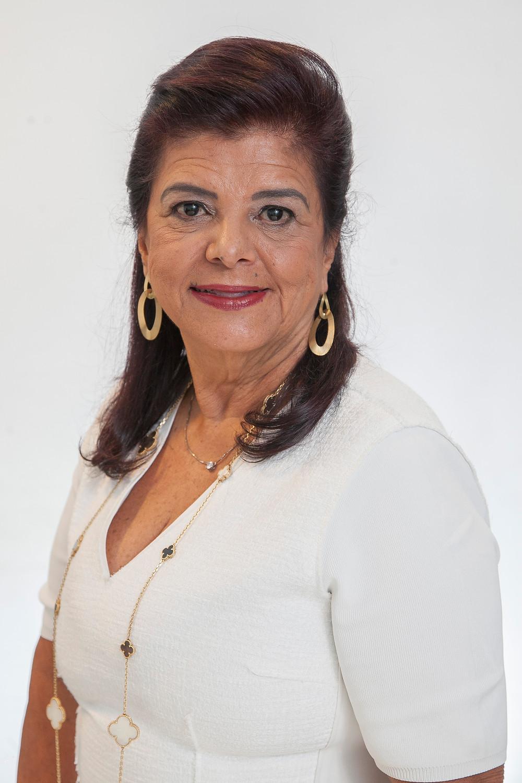 A imagem traz Luiza Helena Trajano, presidente do Magazine Luiza, com blusa branca, brincos e colocares dourados.