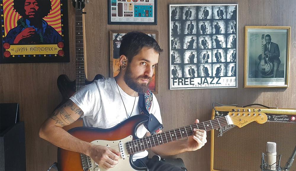 O músico Renan segura a guitarra
