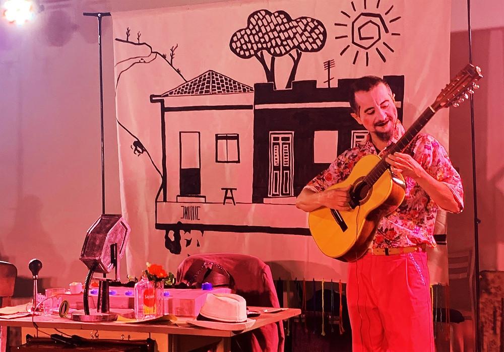 Artista segurando violão para tocar em espetáculo