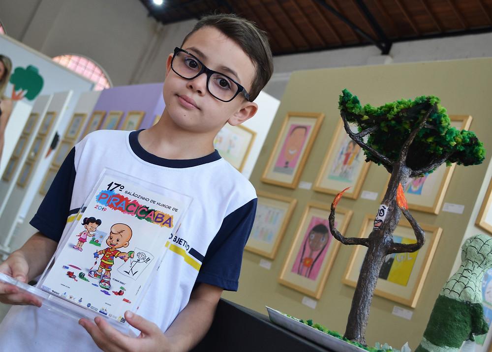 Caio Bonato, 8 anos, com o troféu e ao lado de sua obra vencedora na categoria 7 a 10 anos  - Imagem: Rafael Bitencourt