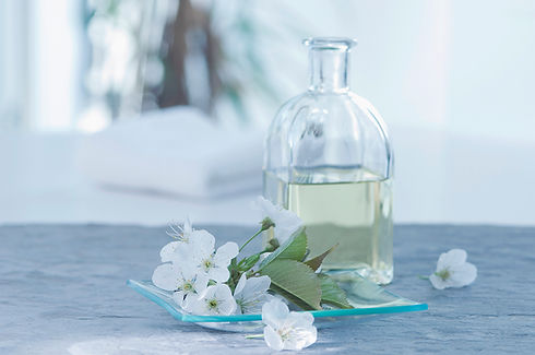 A clear glass bottle containing essential oil set on a grey surface next to a glass bowl of jasmine flowers.