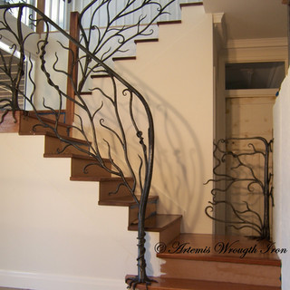 """""""Wild vine"""" wrought iron balustrade features a fully textured and tapered newell post with lower root system, transitioning into a textured top rail, accompanied by other tapered root systems with branches, limbs and vines, wrapping and weaving their way upwards and across the extent of the rails."""