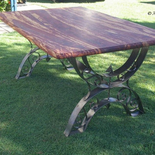 """""""Roman greco""""  Dining table Features a polished iron frame with scrollwork, twisted arrow shafts and solid slab timber top."""