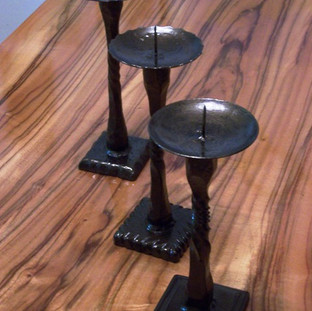 Wrought iron single candle holders with varying textures.