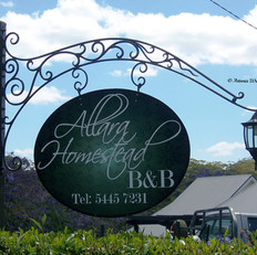 """Allara Homestead"" Wrought iron signage Features tubular lower scroll to conceal lamp wiring."