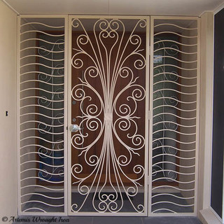 """An """"Art Deco"""" wrought iron security entrance with side panels."""