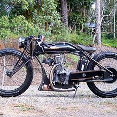 """Boardtrack Racer"". 1916 Indian single cylinder replica racing bike. Features a fully hanbuilt frame, torpedo tank and all associated parts, including wheels, forged front forks and monoshock suspension.  Honda 208cc highly modified ohv industrial engine, manual clutch, single speed."