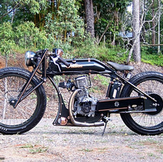 """""""Boardtrack Racer"""". 1916 Indian single cylinder replica racing bike. Features a fully hanbuilt frame, torpedo tank and all associated parts, including wheels, forged front forks and monoshock suspension.  Honda 208cc highly modified ohv industrial engine, manual clutch, single speed."""