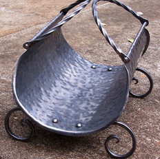 """Firewood holder"" A curved wrought iron and beat rolled sheet metal body, with rivets and twisted iron handles."