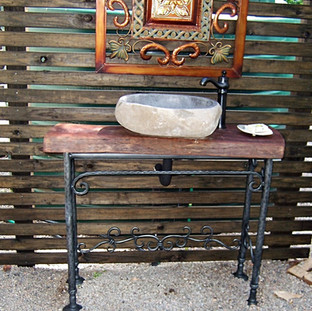 """""""Sweetwater""""  Sink table Features a solid hardwood slab top, wrought iron scroll work and forged legs with non-sinking feet ends."""
