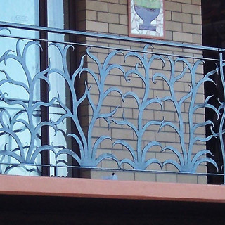 """""""Ferny grove"""" wrought iron balustrade featuring non-repetative individual plant forms with twisted solid iron corner posts wrapped with vines."""