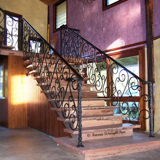 """""""Burlesque"""" wrought iron balustrade features textured/hammered and collar bound newell posts with large full size scrolls fixed to each step."""