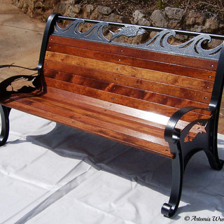"""""""Pisces""""  Park seat Features include an oxy-cut fish silhouette on each arm rest and solid jumping fish and waves across the top, with solid hardwood slats."""