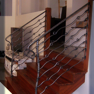 """""""Free form"""" wrought iron balustrade features shackles and rivet fixings with a textured polished finish."""