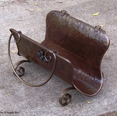 """Firewood holder"" A wrought iron and beat rolled sheet metal body with side flower feature."