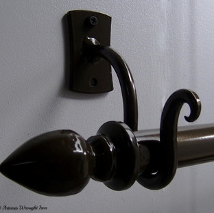 Wrought iron curtain rod hooks and forged curtain rod ends.
