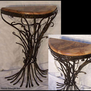 """""""Wild reed""""  Hall table Features a tapered forged waist of hammered bars  and a solid slab timber top."""