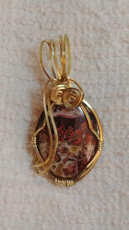 Pendant: wire wrapped orange and brown stone