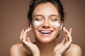 Laughing girl applying moisturizing crea