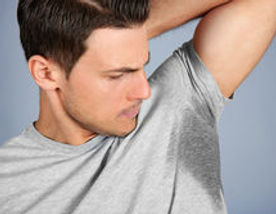 stock-photo-handsome-young-man-with-wet-spot-on-clothes-under-armpit-against-grey-backgrou