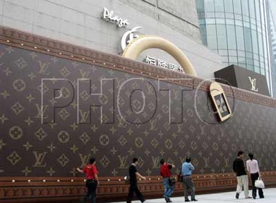 Pedestrians walk past a wall featuring a commercial for Louis Vuitton.