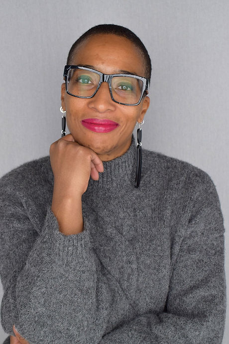 Portrait of Anita Clarke wearing a grey sweater and black glasses