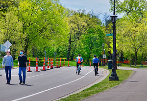 Pedestrians and bicyclists in the southbound lane of Mississippi River Boulevard, which has been closed to car traffic