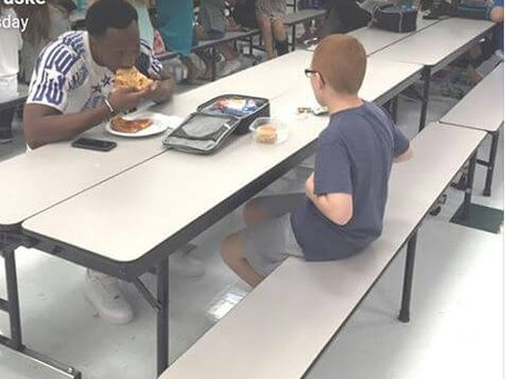 Florida state football player eats lunch with a boy sitting alone